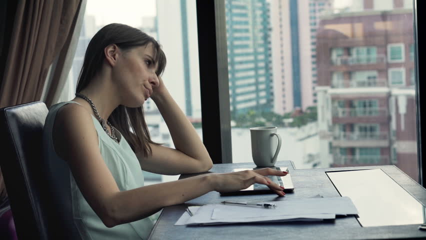 Young bored businesswoman sitting by table in office    Shutterstock HD Video #15988261