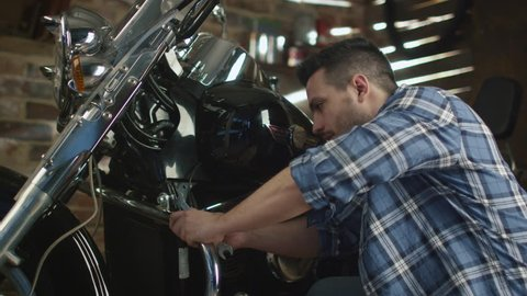Man is tightening nuts with a spanner and repairing his motorcycle in a garage. Shot on RED Cinema Camera in 4K (UHD).