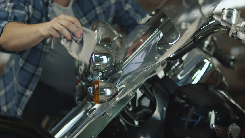 Man is cleaning and polishing chrome objects on his motorcycle in a garage. Shot on RED Cinema Camera in 4K (UHD).