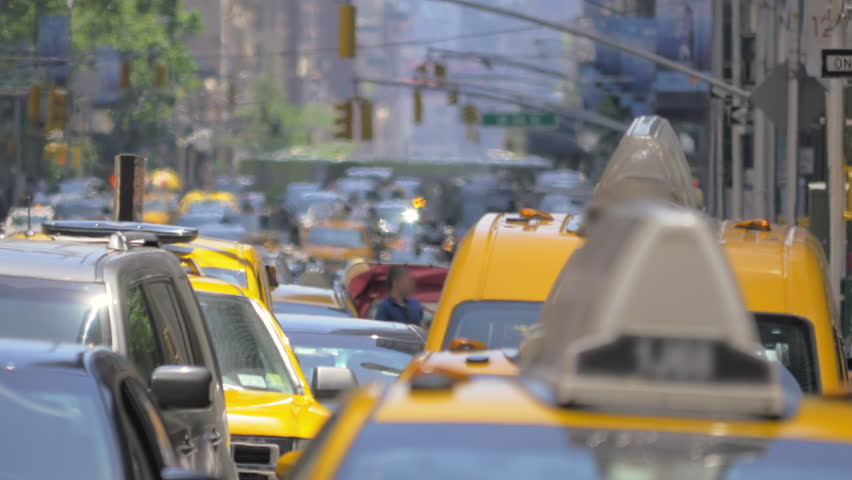 Cars vehicles taxi cabs rush hour congested heavy street traffic Manhattan NYC sunny summer day New York City