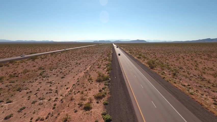 An aerial shot of cars and trucks traveling through the desert of Nevada near Las Vegas on Interstate 15 | Shutterstock HD Video #16022101