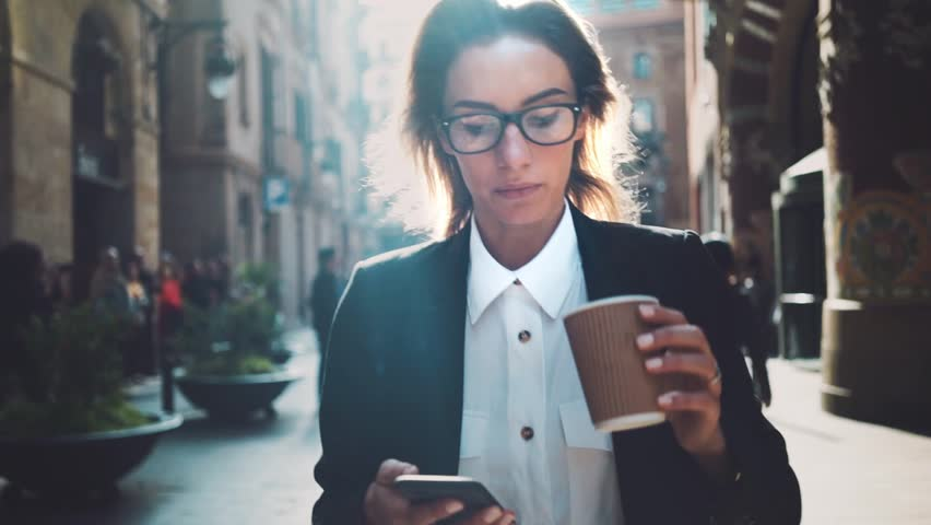 Young professional businesswoman walking on city streets and drinking coffee to go, sunshine, slow motion | Shutterstock Video #16045831