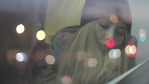 Teenage blonde girl in a beanie and scarf waking up and falling asleep in a public transport next to window with city lights reflection on the window. Exhausted, tired, sleepy woman in a train.