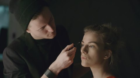 Young male makeup artist brushing eyebrows of a fashion model while preparing her for photo shoot