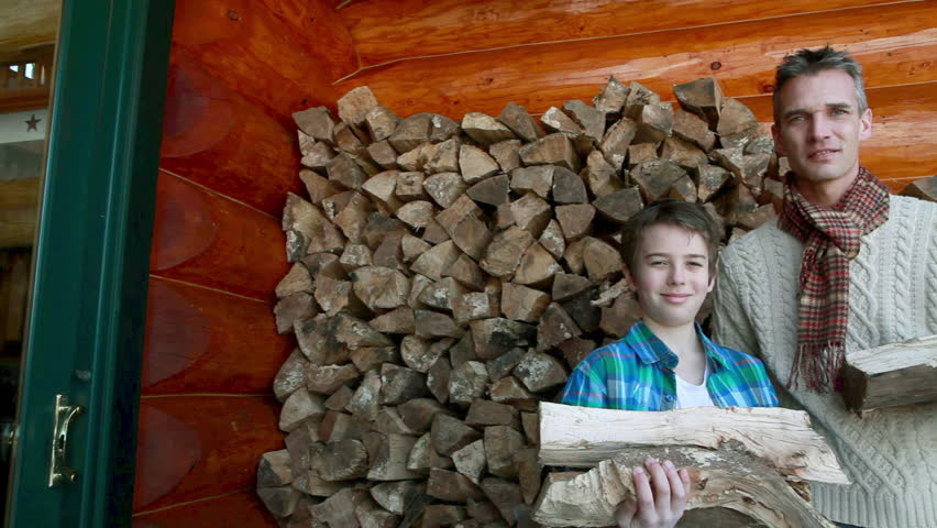 March 03, 2011: Father and son holding logs
