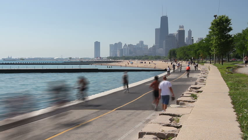 Time lapse of cyclists and runners enjoying a summer day on the Lakefront path along the Lake Michigan shoreline in Chicago.