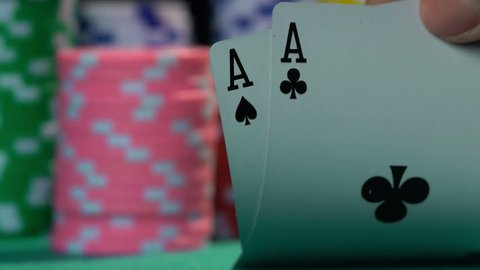 Poker player showing good card combination, one pair of aces in slow motion