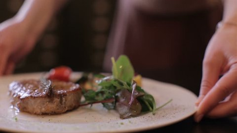 waiter puts pork steak on a table in a restaurant. closeup. Serving Food