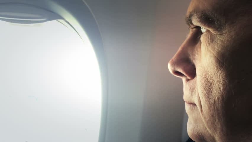 closeup of a businessman looking out the window of a plane