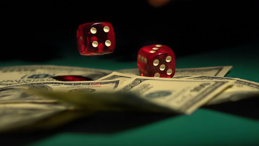Red dice falling on money, gambler playing game at casino, addiction to gambling. Male hands throwing pair of cubes on green table, trying fortune, chance. Successful player winning dollar cash, bet