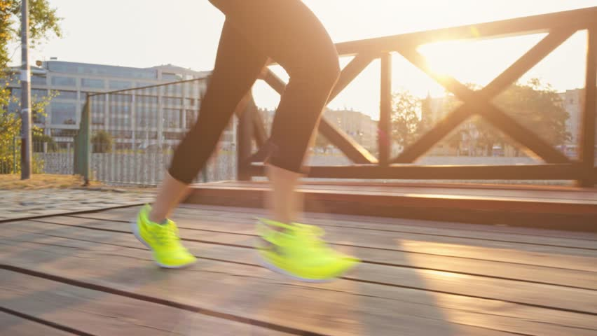 Runner woman feet running in the city exercising outdoors.  stabilized shot 4K. Sportswoman wearing barefoot sports shoes while training on the sunny city bridge. Lens Flare.