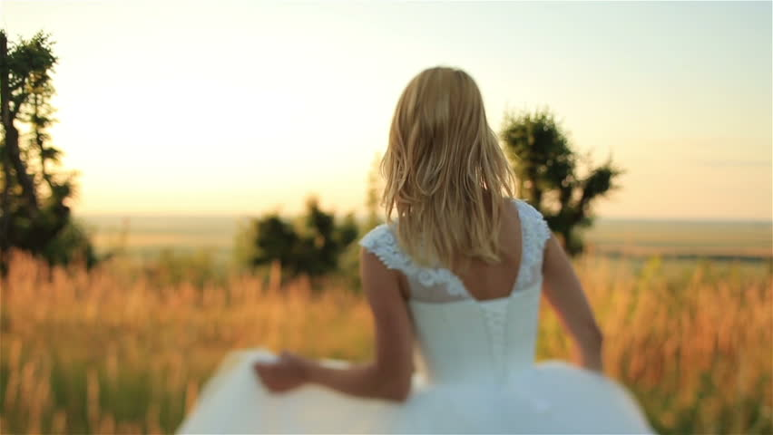 Beautiful blonde bride  in long bridal dress running through the rye field on sunset