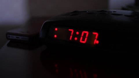 A man sets the time on a digital alarm clock