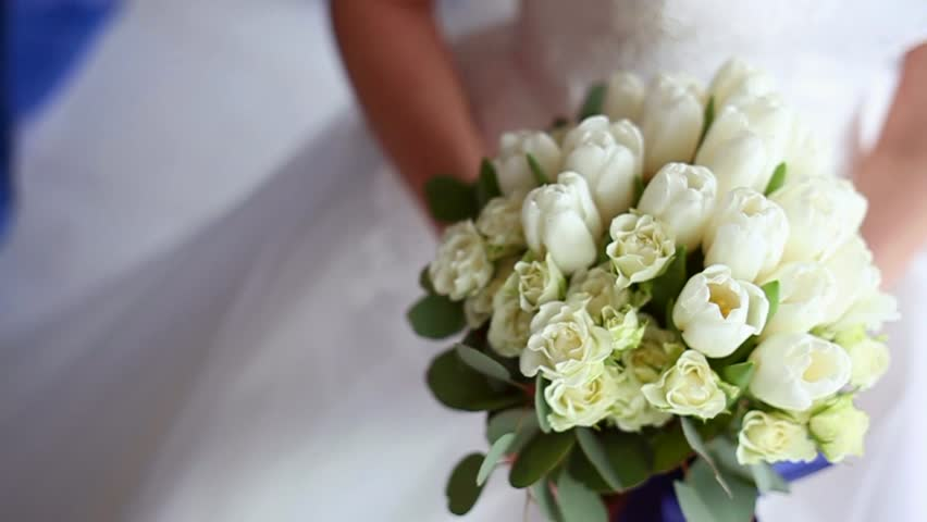 Beautiful bridal bouquet in hands of young bride dressed in white wedding dress. Close up of big bunch of fresh white roses and tulips flowers in female hands. Anonymous bride holding flowers.