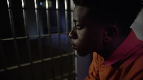 Young man looking out from his prison cell through the bars of jail