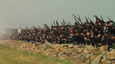 GETTYSBURG, PENNSYLVANIA - JULY 2008 - large-scale, epic Civil War anniversary reenactment -- in the middle of battle.  Wide of Union and Confederate soldiers firing and fighting, cannons and smoke