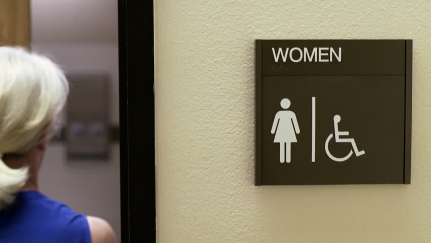 woman walking into a womans restroom in an office