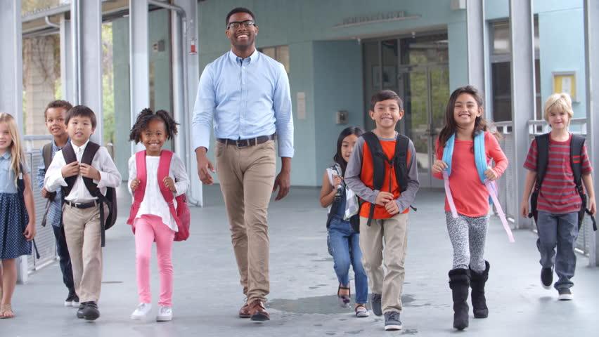 Male teacher walking in corridor with elementary school kids | Shutterstock HD Video #16355911