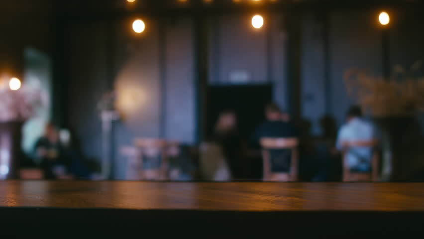 Defocused background - a group of people is sitting in a modern restaurant. Shot with Blackmagic URSA Mini