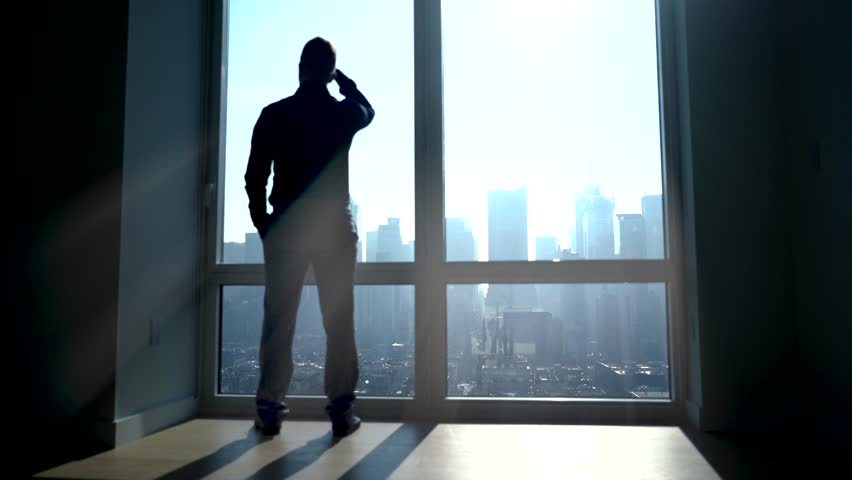 silhouette shadow of one person working in modern office in the morning standing on large window front. startup business idea concept. city panorama background view