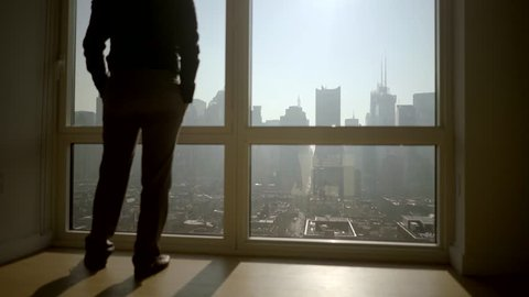 silhouette of one person opening window blinds in the morning looking over city view