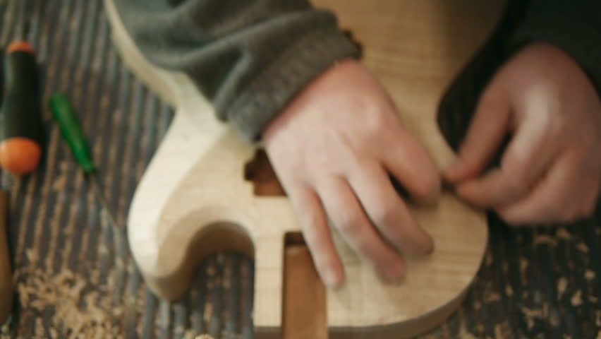Hands of young man at work as craftsman in italian workshop with guitars and musical instruments. Dolly shot