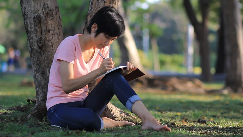 Asian Women with short hair writing In A Diary In The Green Park Outdoors,