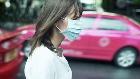 Sad, serious woman in mask walking through the city