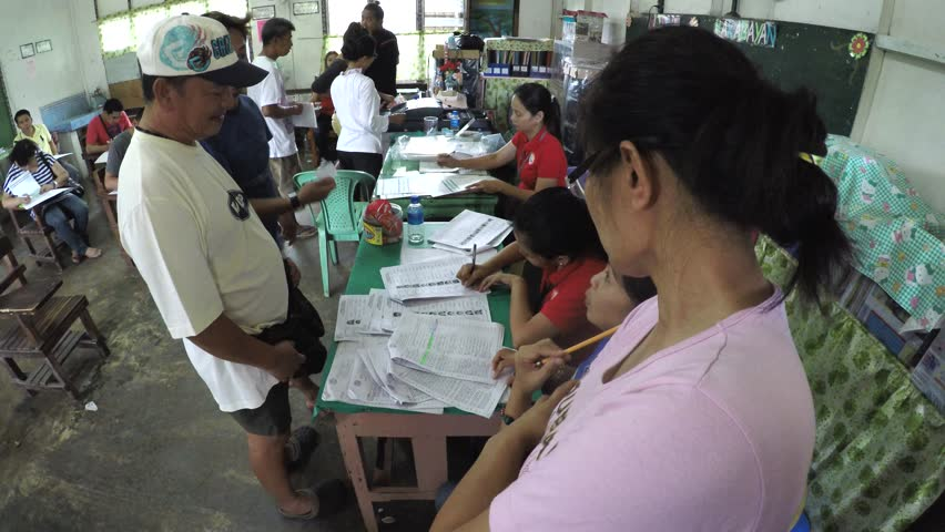 SAN PABLO CITY, LAGUNA, PHILIPPINES – MAY 9, 2016: Board of Election Inspectors BEI assisting voters in election precinct during Philippine presidential election of 2016. #16478131