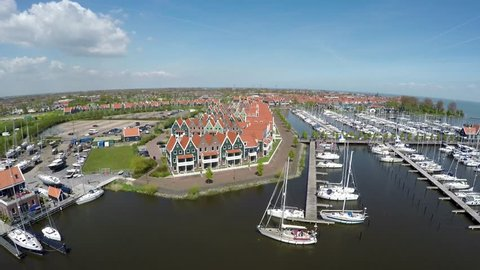 Aerial flying over the recreational harbor of Volendam showing recreational boats ships and typical dutch traditional homes tourist attraction Holland for traditional clothing and old fishing boats 4k