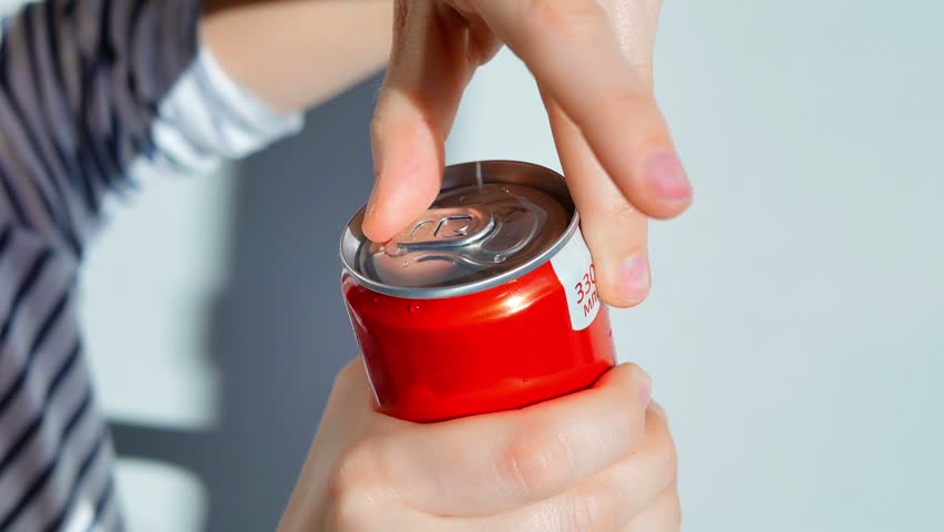 woman opens a soda can