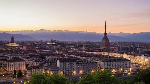 Torino, Italy - May 4, 2016: Turin time lapse, Torino time lapse panoramic cityscape fading from sunset to night. Mole Antonelliana with Torino FC colors in memory of the 1949 Superga airplane crash.