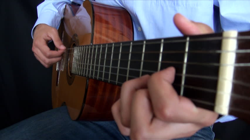 Close up of man playing classical guitar, spanish guitar or acoustic guitar, black background, blur on hand is touching the strings-Adrian