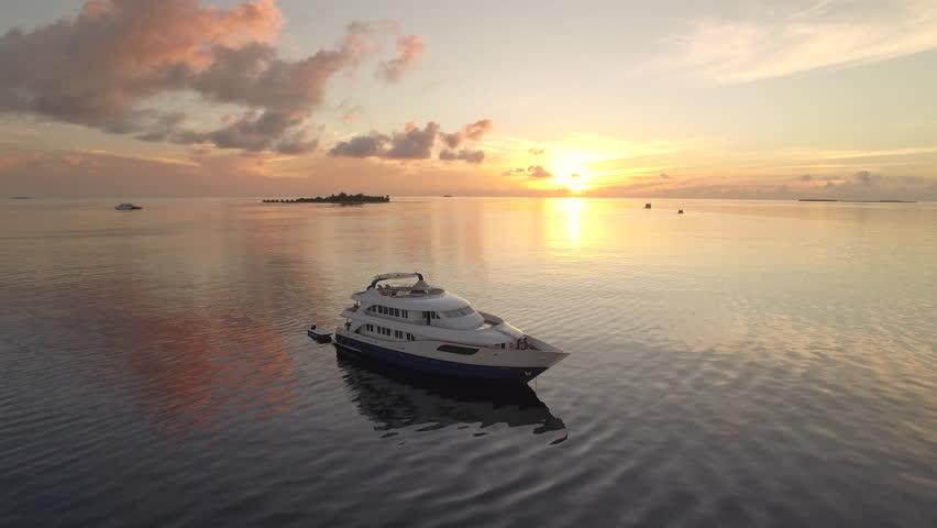 Flight over of luxury boat at tropical sunrise - Maldives Island 2015.   Shutterstock HD Video #16500961