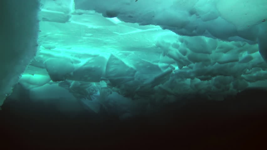 Unique extreme underwater shooting scuba dive beneath ice at geographic  North Pole in cold waters. Fantastic views of the lump of ice in water. ICE CAMP BARNEO, NORTH POLE, ARCTIC - APRIL 2015