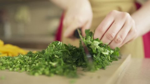 Young woman preparing meal at the kitchen table. Good job for human health. Proper nutrition and wellness. Prepare and chop lush greenery for vegan. Eating at home. Food industry. Close up slow motion