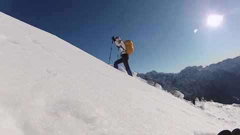 A woman mountain climbing in the snow. - Model Released - HD