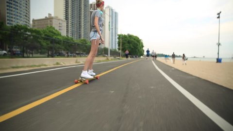 A young woman goes longboard skateboarding with the Chicago, Illinois skyline in the background. - Model Released - 1920x1080 - Full HD
