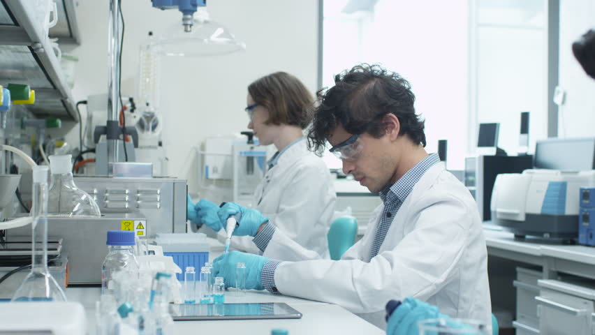 Team of Multiethnic Students in Coats Working in Laboratory of Chemistry Classroom. Shot on RED Cinema Camera in 4K (UHD).