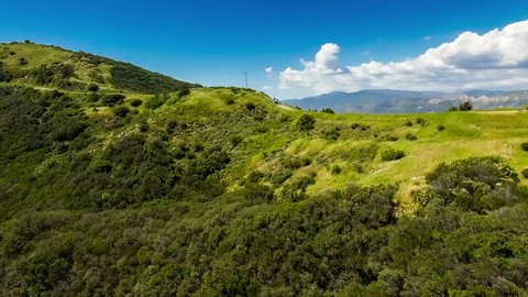 Aerial pass over green rolling hills and California central coast chaparral toward dramatic blue mountain ridges and white clouds, East Camino Cielo near Santa Barbara and Los Padres National Forest