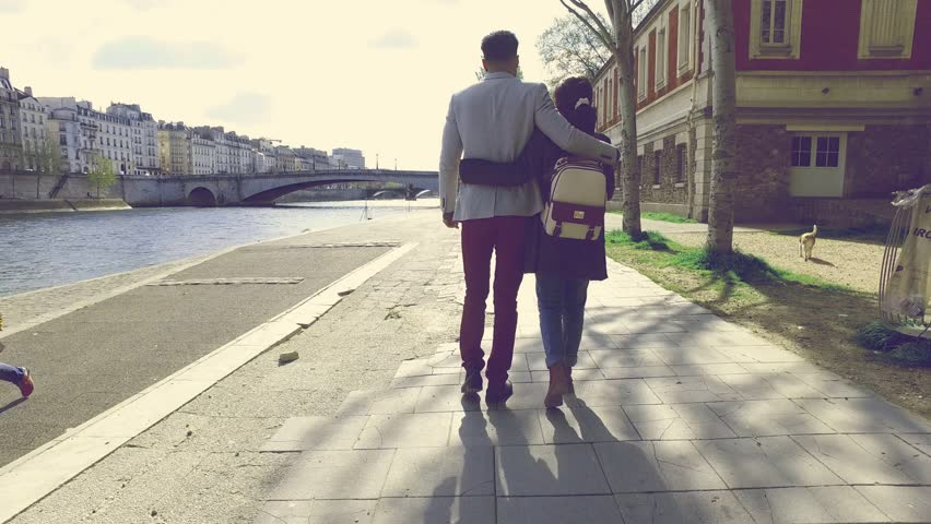 Young couple taking a romantic walk on the banks of the river Seine near Notre Dame cathedral, Paris, France