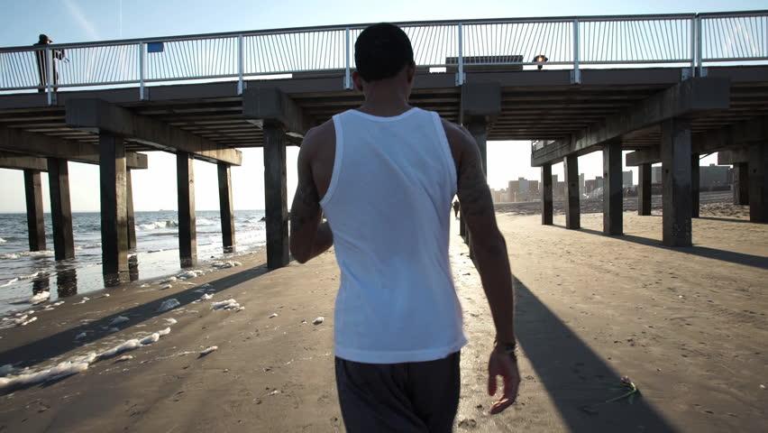 A young, black man runs along the beach. New York, NY - March, 2016