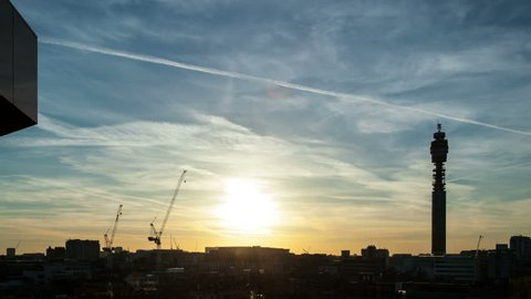 Time lapse of sunset over London rooftops near Tottenham Court Road. Filmed in April 2016 the setting sun silhouettes cranes and the BT Tower and creates a spectacular sky. Shot on DSLR in full 4K.