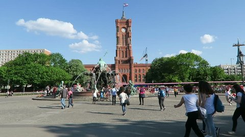 BERLIN, BERLIN/ GERMANY MAY 09 2016: People walking across the Alexanderplatz with its Neptune fountain and the town hall rotes rathaus in Berlin. Camera pan to tv tower.