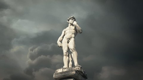 Timelapse: the statue of a greek athlete against a painterly cloudy sky.