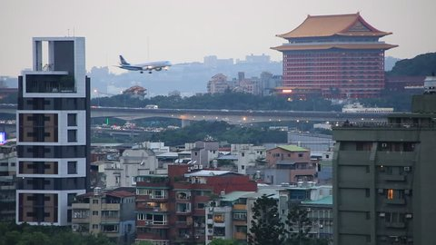 Taipei, Taiwan _ May 12, 2016 : An airplane flying over Taipei city at sunset