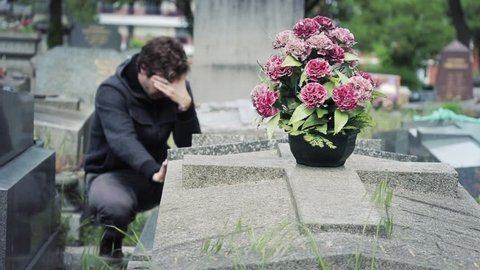 Man Crying In Tomb Of A Cemetery And Then Leaves. Desperate young man crying in tomb of a cemetery and then leaves
