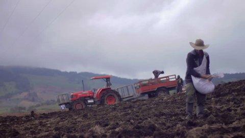 BOYACÁ, COLOMBIA, CIRCA 2014: Farmer spreading seeds across potato field background red tractor