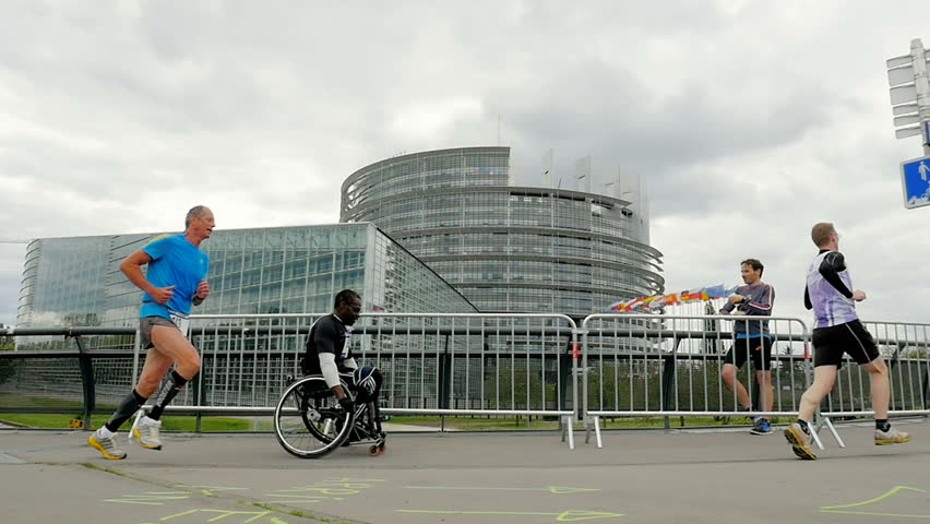 STRASBOURG, FRANCE - CIRCA 2016: Marathon competition with runners and disabled athlete in a sport wheelchair competing in front of the European Parliament - Slow Motion #16748611