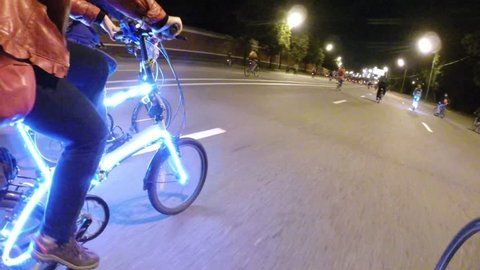 Many cyclists with illumination ride during Night Cycling Parade, FPV